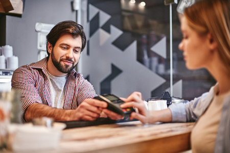 There is nothing shameful about being efficient. Small business, payment, people and service concept - woman with credit card buying coffee at cafe or coffee shop Stock Photo