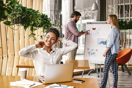 If everyone is moving forward together, then success takes care of itself. Happy businesswoman sitting at her desk and leaning back while stretching Banco de Imagens