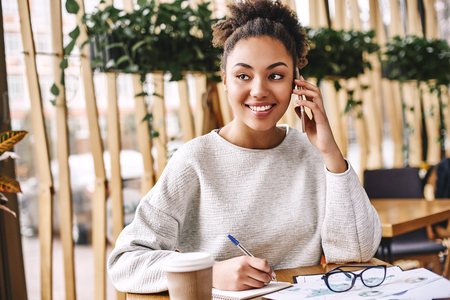 Wonder what your customer really wants? Ask. Don't tell. Attractive business woman working at desk in modern office. Imagens