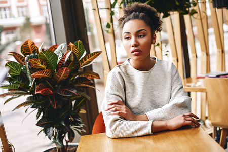 When you find an idea that you just can't stop thinking about, that's probably a good one to pursue. Portrait of attractive african american woman looking thoughtful while sitting at cafe. 版權商用圖片