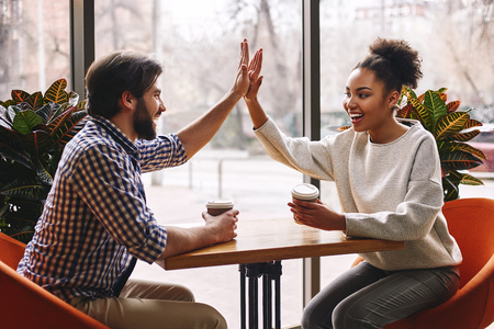 The leadership is about working together. Happy young co-workers giving a high five congratulations as they sit together in a cafeteria enjoying a cup of hot coffee