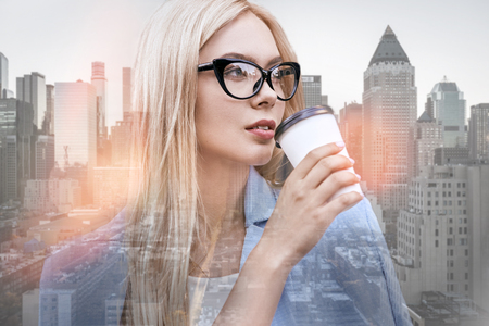 Enjoying her coffee break. Close-up portrait of beautiful business lady with blond hair drinking coffee and looking away while standing outdoors with cityscape on the background Stock Photo