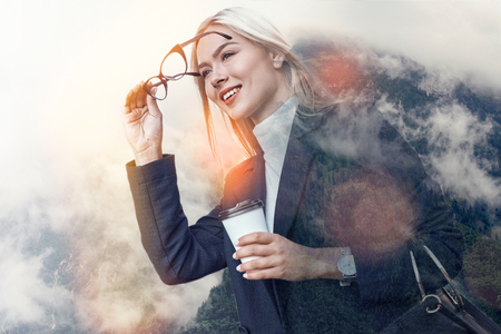 Starting new working day. Cheerful young business woman wearing glasses and drinking coffee while standing against of nature background. Time management. Success concept. Career 版權商用圖片