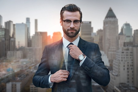 Perfect style. Confident business expert in glasses adjusting necktie while standing against of morning cityscape background. Fashion look. Business style. Success concept