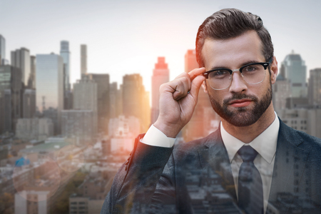 Close-up of young and successful businessman looking at camera and adjusting glasses while standing outdoors with cityscape on the background. Business look. Success concept.