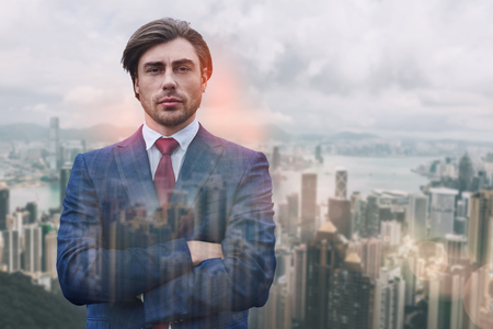 Succesful and rich. Close-up portrait of attractive man in suit keeping his arms crossed while standing against of cityscape background. Business concept. Success.