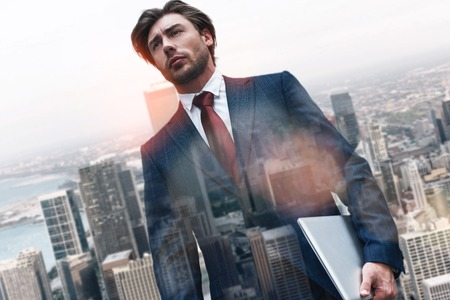 Confidence with technologies. Portrait of handsome businessman holding laptop while standing against of morning cityscape background. Digital technologies. IT specialist