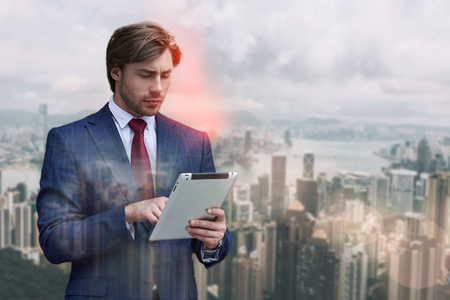 Checking his mail. Handsome bearded businessman in suit using digital tablet while standing against of cityscape background. IT specialist. Digital concept