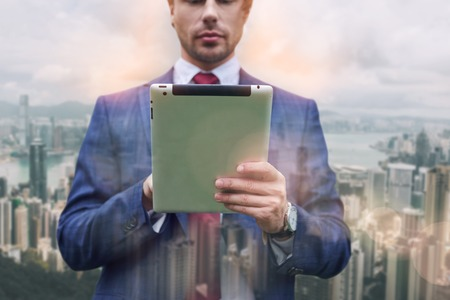 Confident IT expert. Close-up portrait of businessman in suit using digital tablet while standing against of cityscape background. Stock fotó