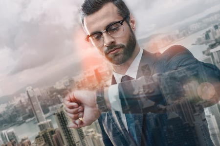 Debería estar allí a tiempo. Hombre de negocios confiado en traje mirando su reloj mientras está parado al aire libre con modernos edificios de oficinas en el fondo