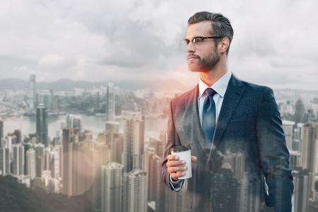 Beginn des neuen Arbeitstages. Erfolgreicher junger Geschäftsmann, der eine Tasse Kaffee hält und wegschaut, während er im Freien steht Standard-Bild
