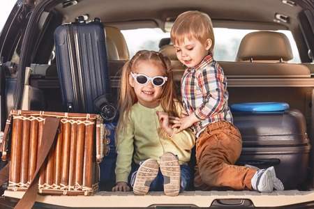 Beginning of the trip. Little cute kids playing in the trunk of a car with suitcases. Family road trip