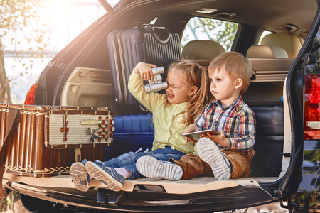 Little cute kids having fun in the trunk of a car with suitcases. Family road trip