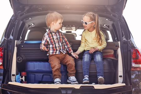 The best education you will ever get is traveling. Little cute kids in the trunk of a car with suitcases. Family road trip Foto de archivo