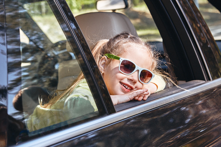 Cute cheerful little caucasian girl sitting inside the car, looking out the window and smiling at the camera. Family road trip