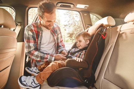 Traveling in the company of those we love is home in motion. Father fastening his baby boy that sitting in a car in safety chair. Family road trip Stockfoto