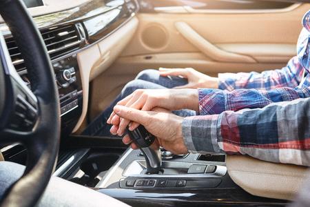 Una vita di avventure. Primo piano di giovani coppie che si tengono per mano insieme in auto. Viaggio in famiglia