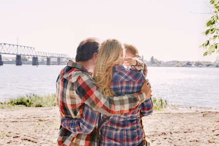 The memories we make with our family is everything. Happy family hugging in a park. Summertime, relax, family unity
