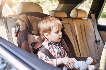 Boy sitting in a car in safety chair. Family road trip Imagens