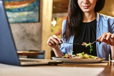 Snack time heals all wounds. Businesswoman having lunch in companys restaurant. Cozy interior Standard-Bild