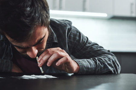Drug addiction is a self-punishing disease that ruins mental, psychological and physical health. Man snorts a line of cocaine with a rolled up bank note. Close up Stock Photo