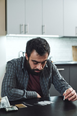 The dead drug leaves a ghost behind. At certain hours it haunts the house. Man preparing to snort a line of cocaine with a rolled up bank note. Close up Stock Photo