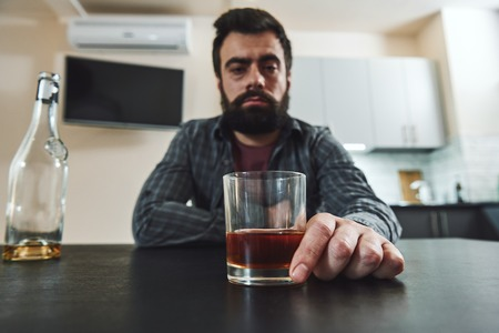 The most terrible poverty is loneliness. Drunk man with glass of whiskey and empty bottle sitting at table in kitchen. Drinking alone. Male alcoholism concept. Selective focus. Front view