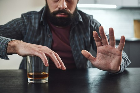 Forget past mistakes. Forget failures. Forget about everything except what you're going to do now – and do it. Addicted man refuses to drink a glass of whiskey. Cropped image. Selective focus