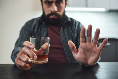 I am more afraid of alcohol than of all the bullets of the enemy. Addicted man refuses to drink a glass of whiskey. Cropped image. Selective focus