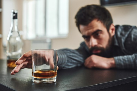 You have to break down before you can break through. Alcohol abuse: drunk man lying down on a table looking at a glass of whiskey. Selective focus