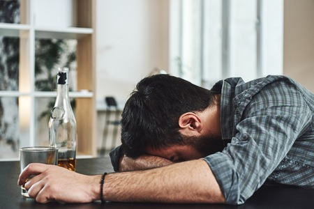 Drunkenness is temporary suicide. Alcohol abuse: drunk man lying down on a table with glass of whiskey still in hand Stock Photo - 118553791