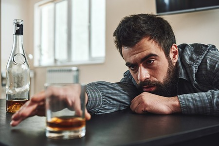 The best way out is always through. Alcohol abuse: drunk man lying down on a table looking at a glass of whiskey. Selective focus Stock Photo