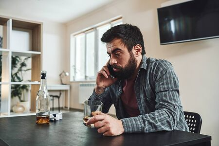 Drunk man with glass and bottle of whiskey in kitchen.