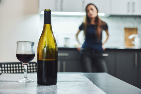 You don't get over an addiction by stopping using. You recovery by creating a new life where it's easier to not use. A bottle and glass of wine on the table. Addicted woman standing in the background