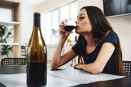 Addiction is a symptom of not growing up. Young woman drinking red wine alone in kitchen at home. Female alcoholism concept. Protest in the treatment of alcohol addiction.