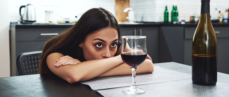 Recovery is not for people who need it, it's for people who want it. Drunk girl looking at bottle of alcohol. Soccial issue alcoholism. Stok Fotoğraf