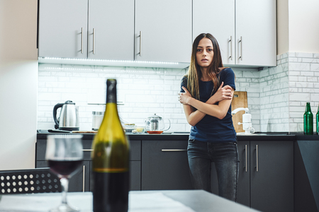 My recovery must come first so that everything I love in life doesn't have to come last. Young addicted, depressed woman standing in the kitchen, looking at the bottle of red wine on the table Reklamní fotografie