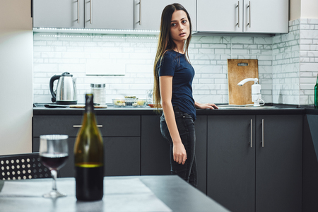 It does not matter how slowly you go as long as you do not stop. Young addicted, depressed woman standing in the kitchen, looking away Stock fotó
