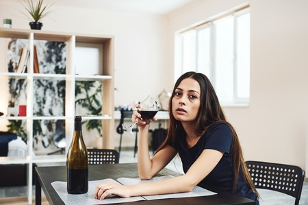Alcoholism is a disease of the whole person. Young woman drinking red wine alone in kitchen at home. Female alcoholism concept. Protest in the treatment of alcohol addiction.