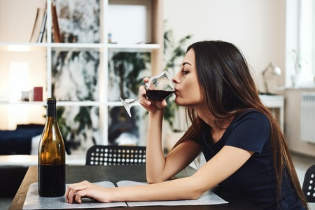 When the wine goes in, strange things come out. Young woman drinking red wine alone in kitchen at home. Female alcoholism concept. Protest in the treatment of alcohol addiction. Stok Fotoğraf