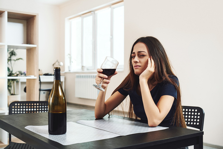 The first thing in the human personality that dissolves in alcohol is dignity. Young woman drinking red wine alone in kitchen at home. Female alcoholism concept. Protest in the treatment of addiction. Stok Fotoğraf