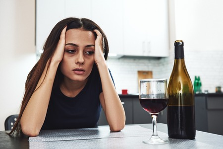 Se volverá más difícil antes de que se vuelva más fácil. Pero mejorará, solo tienes que superar las cosas difíciles primero. Chica borracha mirando una botella de alcohol. Alcoholismo problema social.