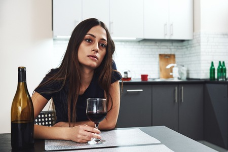 Recovery is an acceptance that your life is in shambles and you have to change. Young addicted, depressed woman with red wine sitting in the kitchen, looking away