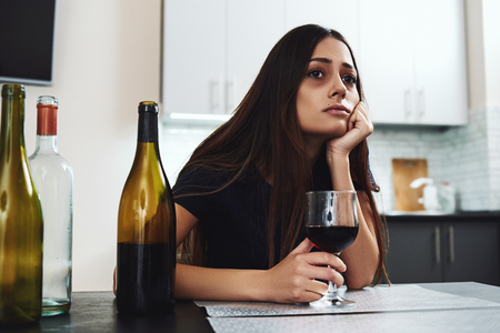 You were never created to live depressed, defeated, guilty, condemned, ashamed or unworthy. Young addicted, depressed woman with red wine sitting in the kitchen, looking away