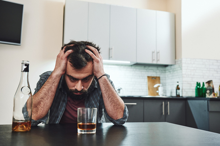 I became a very angry person and it was all due to alcoholism. Drunk man with glass and bottle of whiskey sitting at table in kitchen. Drinking alone. Male alcoholism concept Stock Photo