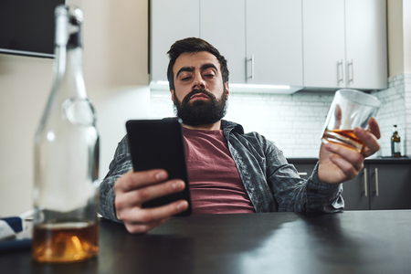 People can be more forgiving than you can imagine. But you have to forgive yourself. Let go of what's bitter and move on.Young man alcoholic, social problems concept, sitting, drinking whiskey