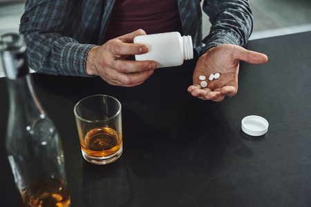 Depression is living in a body that fights to survive, with a mind that tries to die. Close up of man sitting at table with alcohol and drugs. Alcoholism concept Stock Photo