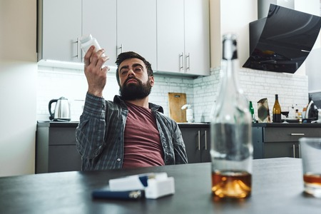 If you are chronically down, it is a lifelong fight to keep from sinking. Drunk man sitting at table with alcohol and drugs. Alcoholism concept 스톡 콘텐츠