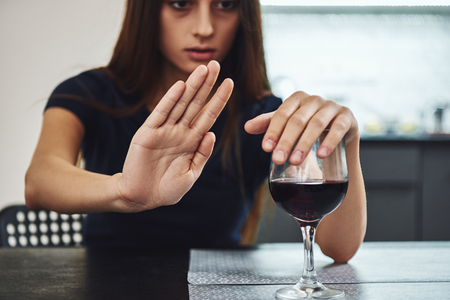 Recovery is something that you have to work on every single day and it's something that doesn't get a day off. Addicted woman refuses to drink a glass of red wine. Close up