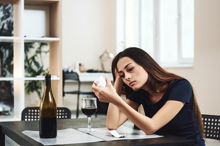 The unfortunate thing about this world is that good habits are so much easier to give up than bad ones. Addicted woman taking drugs with alcohol